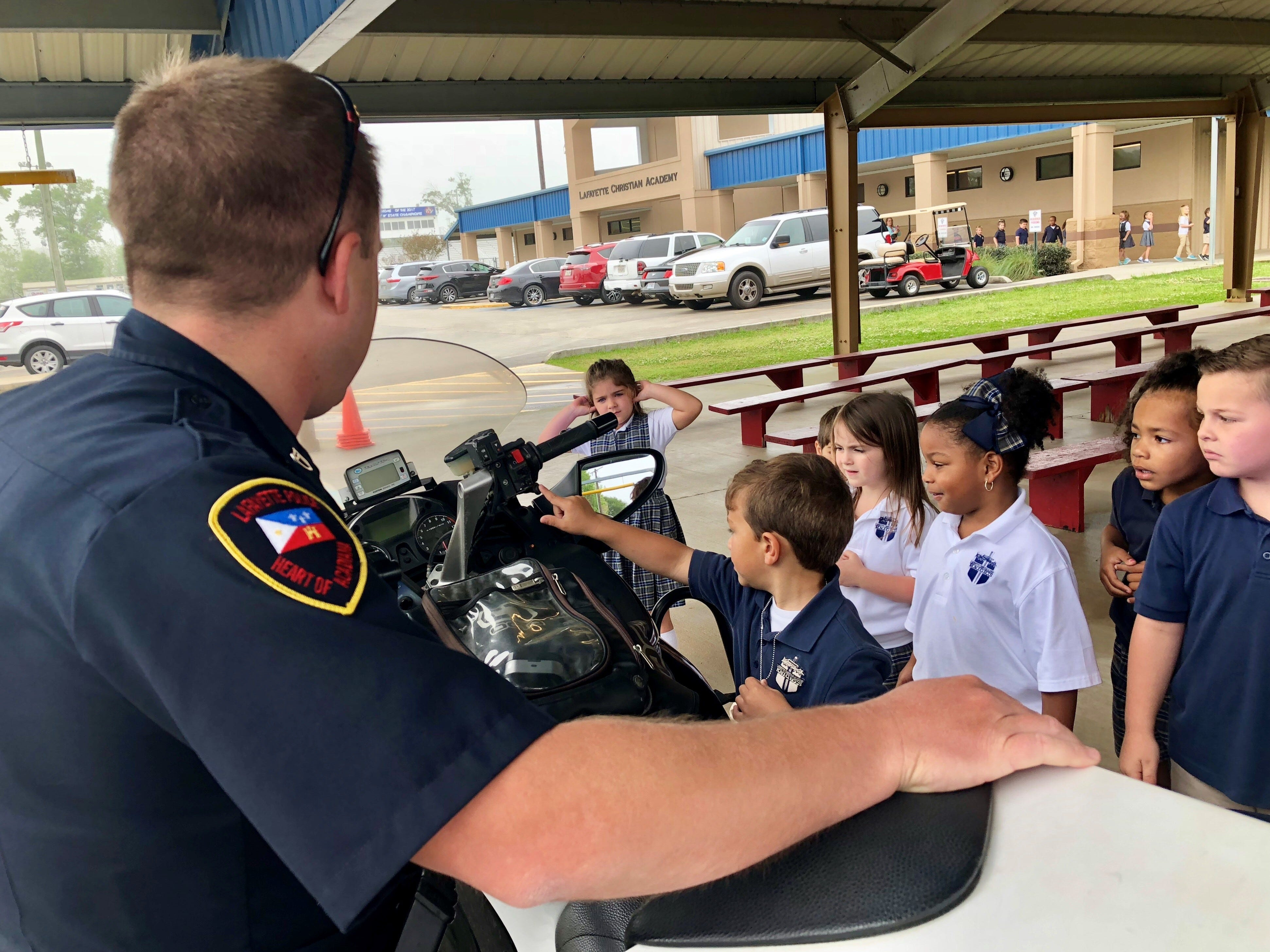 Lafayette Police officers visit with Lafayette Christian Academy students in pre-K, kindergarten and first grade Friday, April 5. Kids check out an officer's motorcycle and even try the siren.