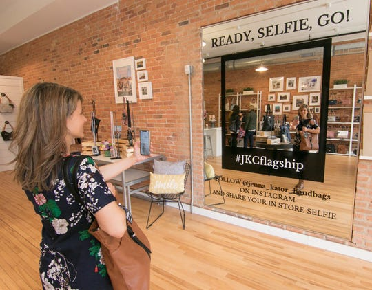 Jenna Kator describes her new brick-and-mortar store as a destination, as she demonstrates the selfie mirror while wearing a purse inspired by Howell, Friday, April 5, 2019.