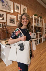 "Jenna Kator models one the purses she designed, named ""Fowlerville"" after the Livingston County farming community, at her newly opened storefront in downtown Howell Friday, April 5, 2019."