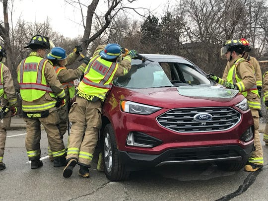 Firefighters from the Brighton Area Fire Authority work to remove the windshield of a 2018 Ford Escape during an extrication demonstration Friday April 5, 2019.