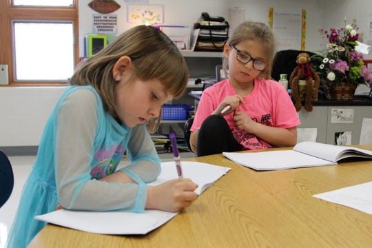 Taft Elementary first grader Kalista Keen jots down sentences while classmate Raven Young watches during a 30-minute small group session on Thursday.
