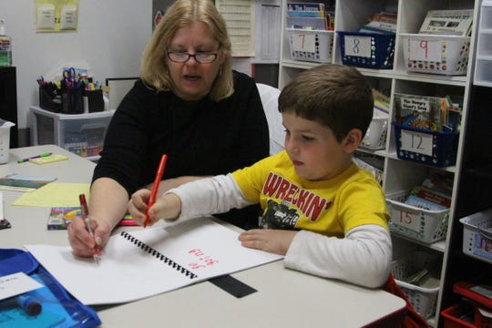 Cheryl Palm, a Reading Recovery teacher at Taft Elementary, goes through a lesson with first grader Braxston Fields-Porter on Wednesday.