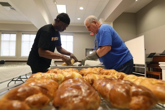 Steve Johnson, left, and John Kay help arrange hundreds of loaves of sweet bread in preparation for the Memphis Greek Festival at Annunciation Greek Orthodox Church on April 5.
