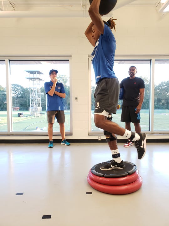 Memphis quarterback Markevion Quinn works out during his rehabilitation from an ACL injury. The workout is overseen by Memphis senior assistant athletic trainer Larry Reynolds (right)