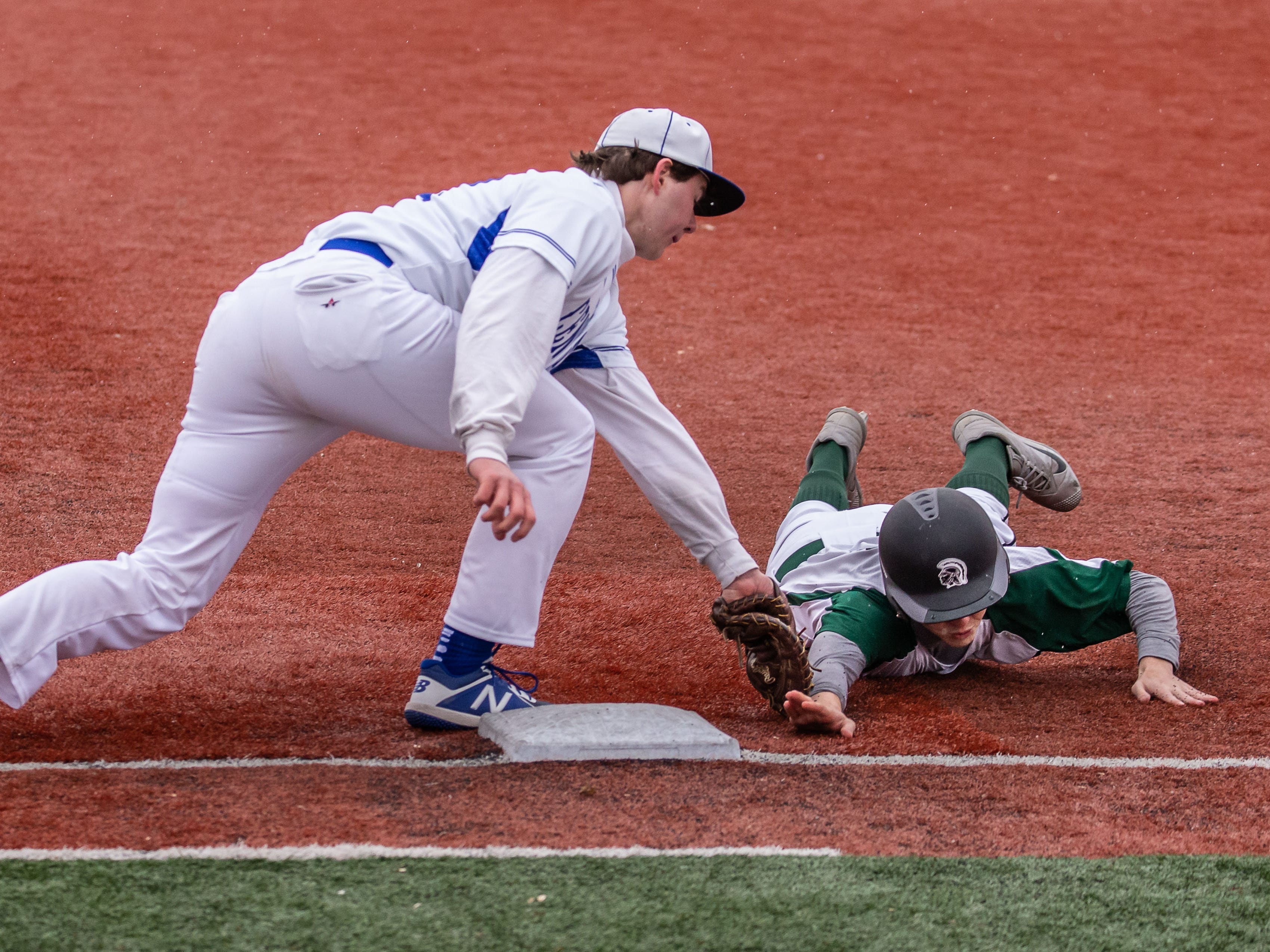 Brookfield Central first baseman Luke Schmidt (22) tags out Wauwatosa West's Will Baran (7) during the game at Brookfield Central on Thursday, April 4, 2019.