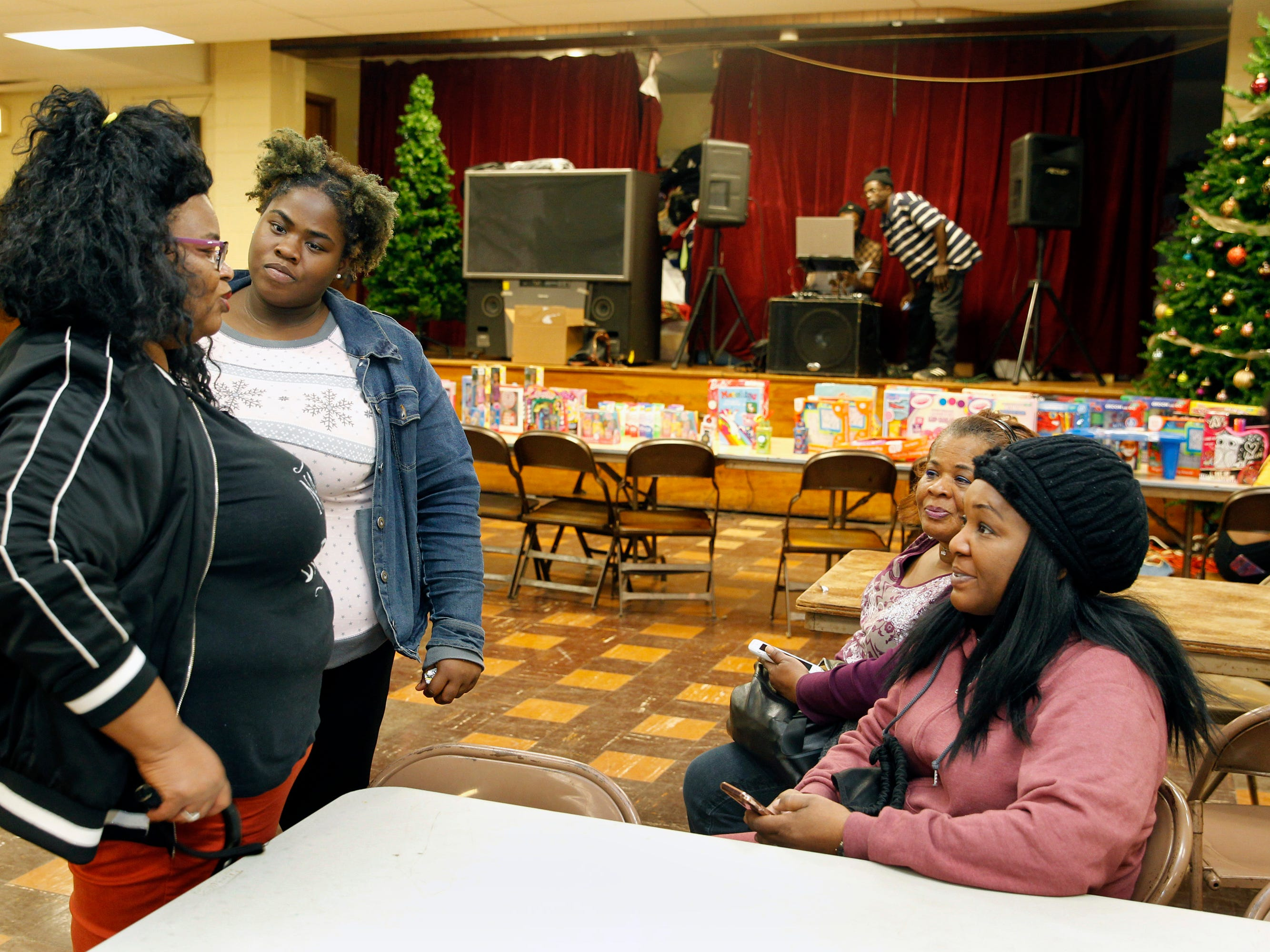 Gloria Nichols, left, stands next to her daughter, Tia James, as they talk to supporters of her nonprofit, Robert's Way, during a holiday event that it held.
