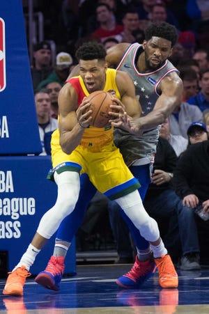 Philadelphia 76ers center Joel Embiid pressures Bucks forward Giannis Antetokounmpo on Thursday night.