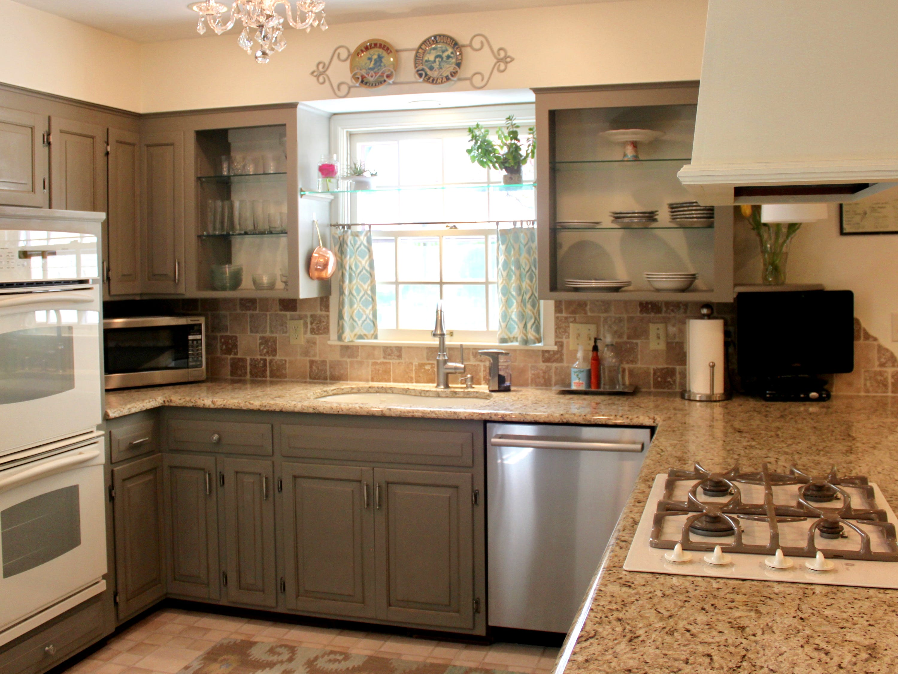 Sarah Timmer updated the kitchen of her previous home by taking the doors off some of the cabinets and exposing the shelves. Painting the  cabinets, changing the lighting and adding new hardware also provided a new look.