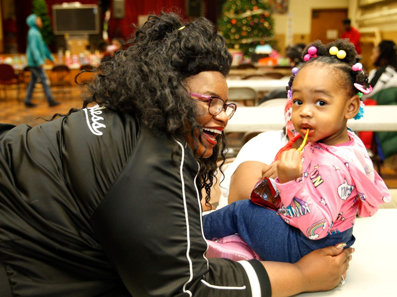 Gloria Nichols enjoys a happy moment with her granddaughter, Kensley Williams, 2, during a holiday event held by her nonprofit, Robert's Way.