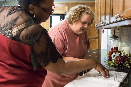 G.B. Cooley Emerson House manager Samanthia Copeland, left, helps resident Tracy Pheles pick a dinner menu item from the house menu book on her night to prepare dinner in Monroe, La. on April 5. Despite Emreson House residents being more self-reliant, they still need help and supervision from staff to complete daily chores around the house. The parishwide organization operates community homes in the area which provides round-the-clock care to persons with intellectual disabilities