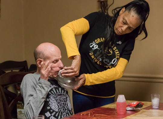 "Yolanda Bethly, the house manager, wipes Royce Shivers' mouth after his afternoon snack at the G.B. Cooley Shannon House in Monroe, La. on April 5. ""After 30 years, it's not like work anymore. It's like home,"" Bethly said about caring for the residents. The parishwide organization operates community homes in the area which provides round-the-clock care to persons with intellectual disabilities"