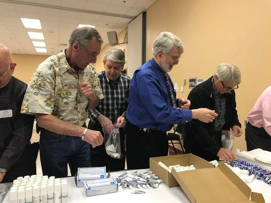 Monroe Rotary Club members pack hygiene kits Thursday.
