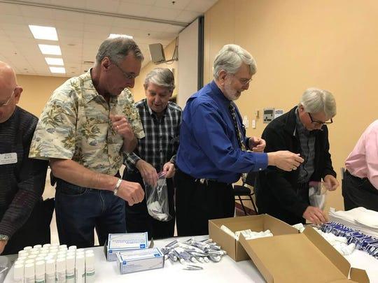 Monroe Rotary Club members pack hygiene kits Thursday.