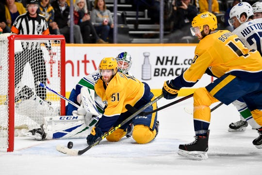 Nashville Predators center Nick Bonino (13) scores past Vancouver Canucks goaltender Jacob Markstrom (25) with left wing Austin Watson (51) during the third period at Bridgestone Arena in Nashville, Tenn., Thursday, April 4, 2019.