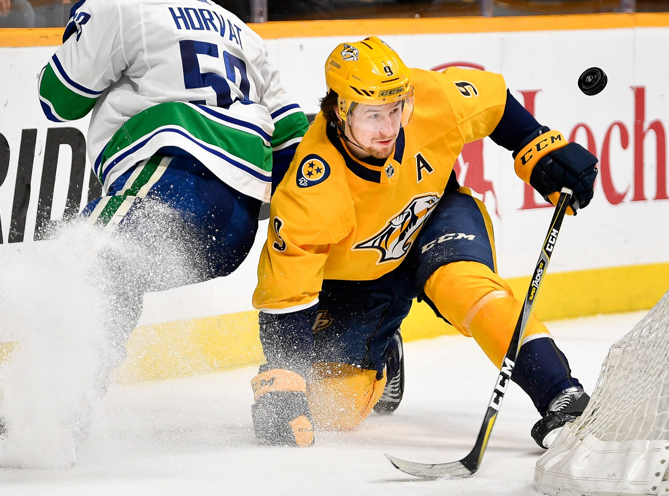 Nashville Predators left wing Filip Forsberg (9) watchers the puck next to Vancouver Canucks center Bo Horvat (53) during the second period at Bridgestone Arena in Nashville, Tenn., Thursday, April 4, 2019.