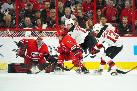 New Jersey Devils center Nico Hischier (13) takes a second period shot against Carolina Hurricanes defenseman Justin Faulk (27) and goaltender Petr Mrazek (34) at PNC Arena.