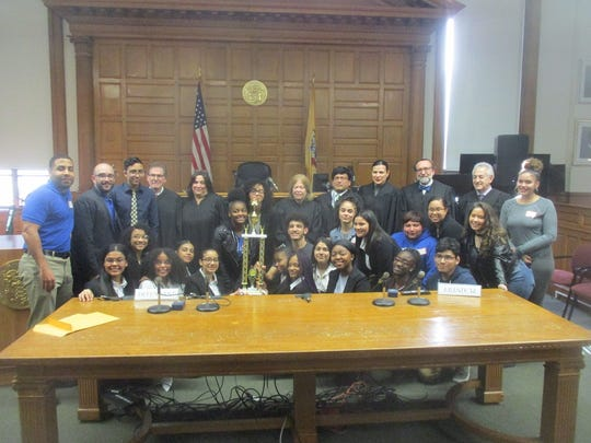 Students from Paterson's HARP Academy pose with their first place trophy for best overall high score in the  first annual Spring Intermural Mock Trial Competition.