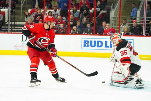 New Jersey Devils goaltender Cory Schneider (35) stops the second period breakaway shot by Carolina Hurricanes center Sebastian Aho (20) at PNC Arena.