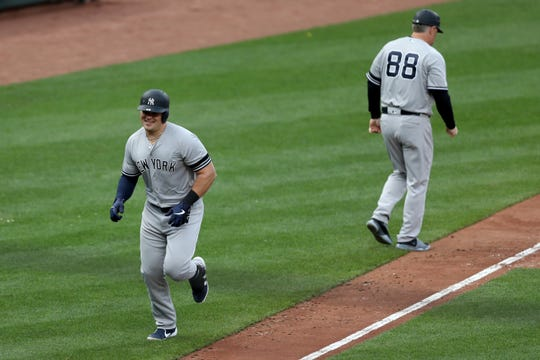 Luke Voit of the New York Yankees high fives third base coach Phil Nevin #88 after hitting a three run home run against the Baltimore Orioles in the eighth inning at Oriole Park at Camden Yards on April 04, 2019 in Baltimore, Maryland.
