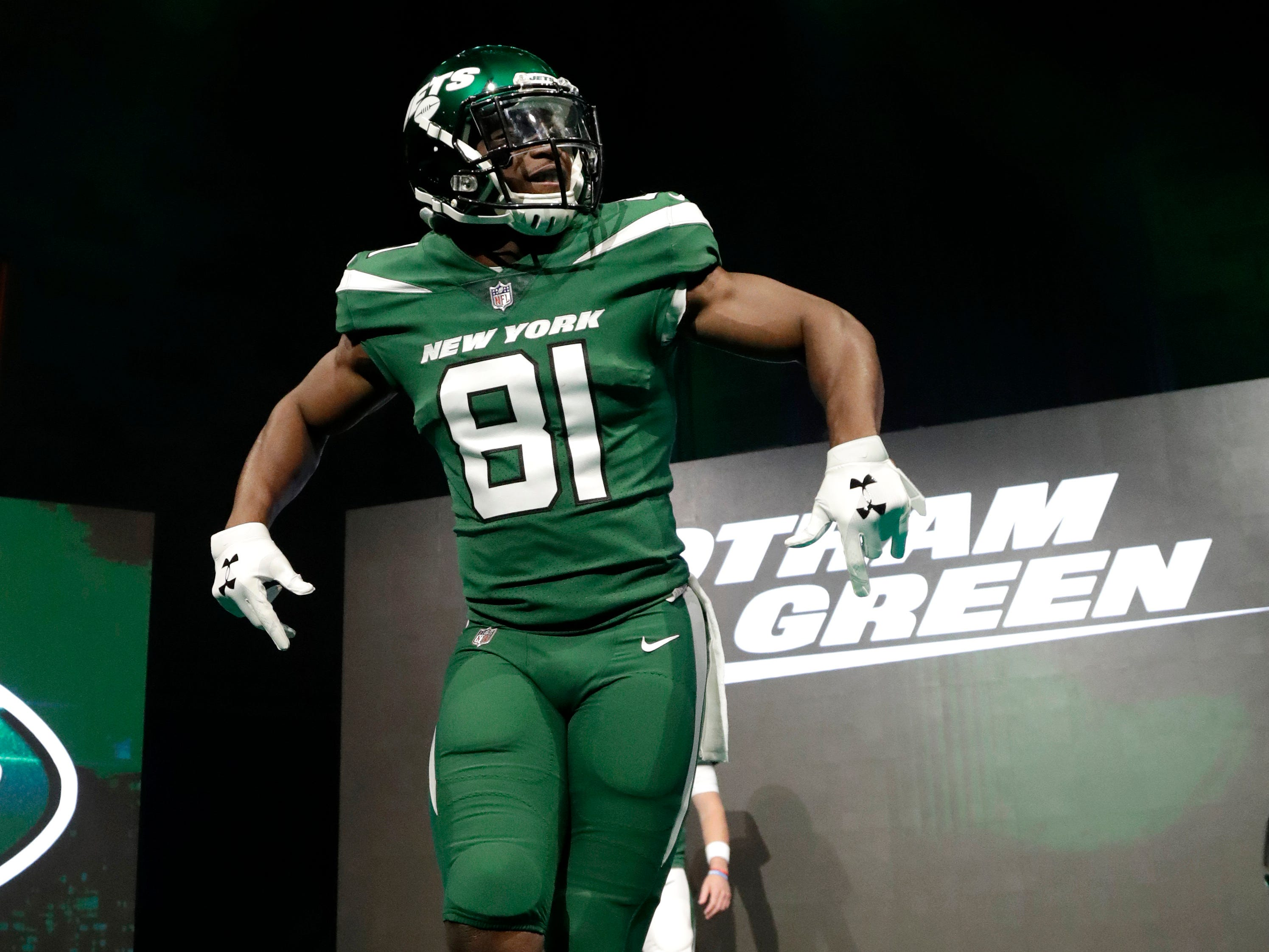 "New York Jets wide receiver Quincy Enunwa models the NFL football team's new ""Gotham green"" uniform Thursday, April 4, 2019, in New York. (AP Photo/Julio Cortez)"