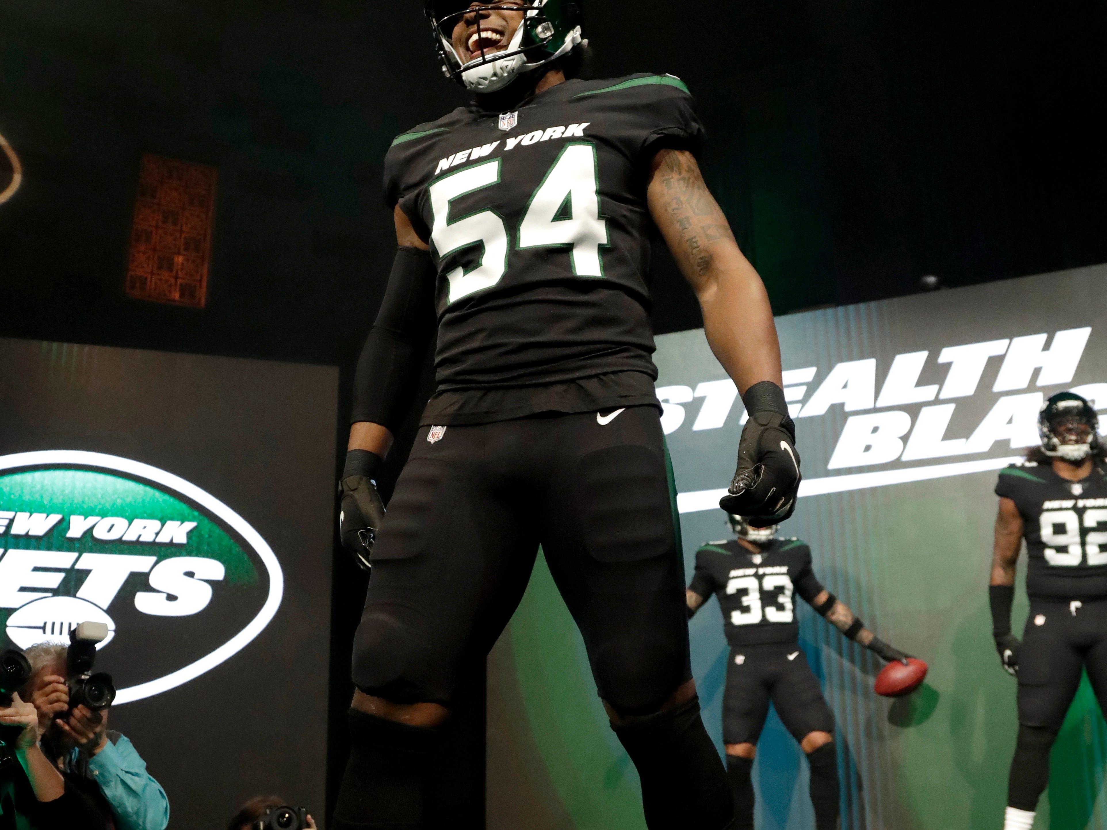 "New York Jets inside linebacker Avery Williamson models the NFL football team's new ""stealth black"" uniform Thursday, April 4, 2019, in New York. (AP Photo/Julio Cortez)"