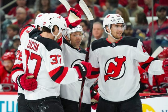 New Jersey Devils defenseman Andy Greene (6) celebrates his first period goal with center Pavel Zacha (37) and  center Michael McLeod (41) against the Carolina Hurricanes at PNC Arena.