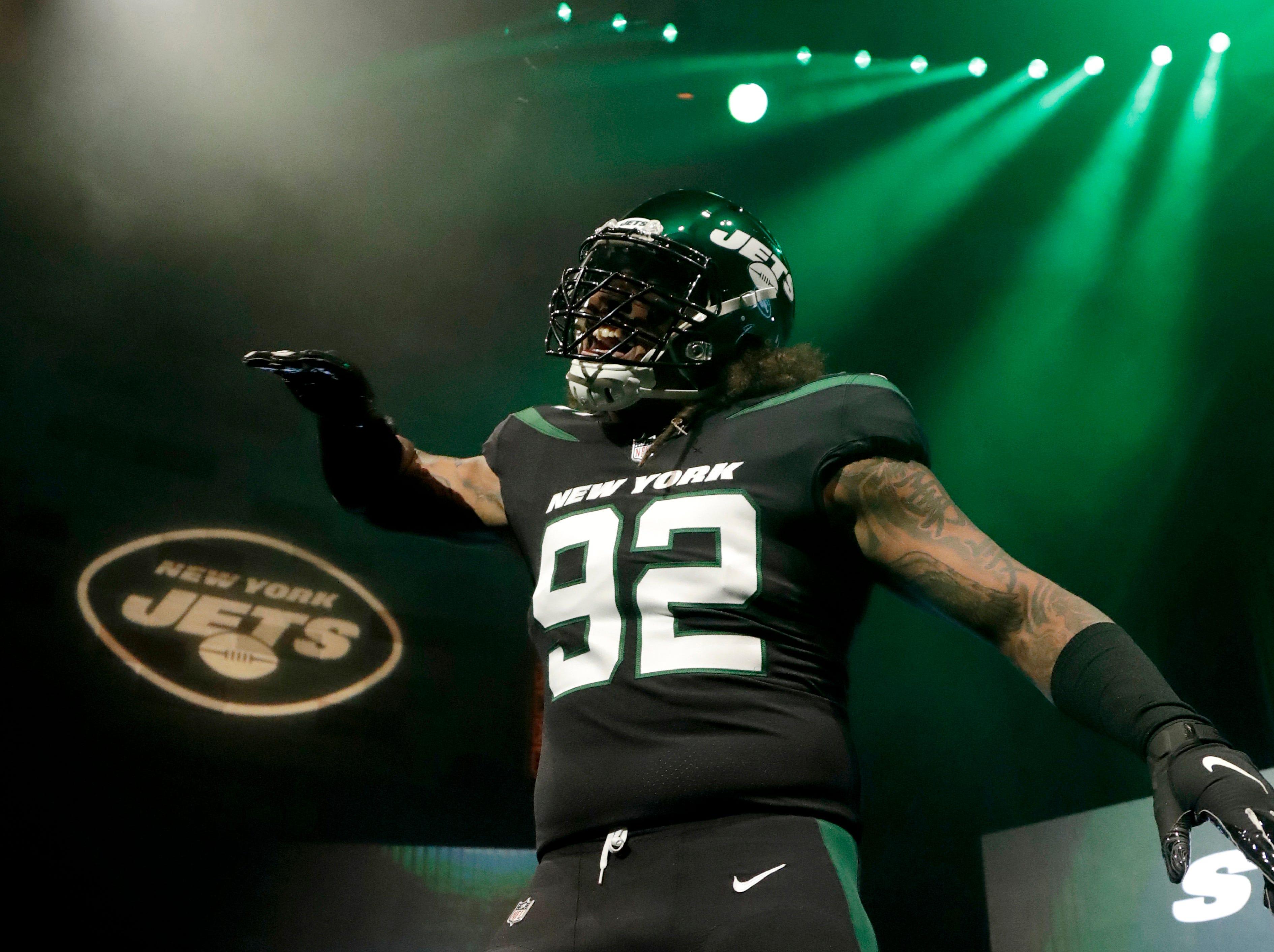 "New York Jets defensive end Leonard Williams models the NFL football team's new ""stealth black"" uniform Thursday, April 4, 2019, in New York. (AP Photo/Julio Cortez)"