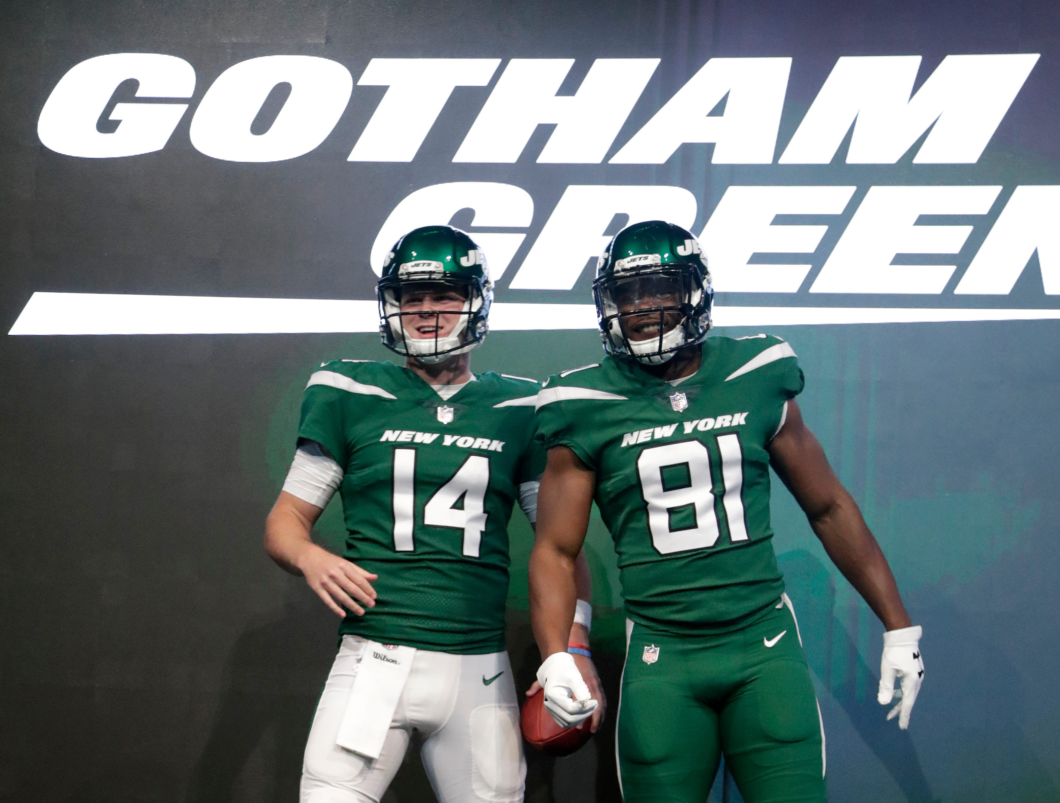 """New York Jets quarterback Sam Darnold (14) and wide receiver Quincy Enunwa (81) model the NFL football team's new """"Gotham green"""" uniforms Thursday, April 4, 2019, in New York. (AP Photo/Julio Cortez)"""