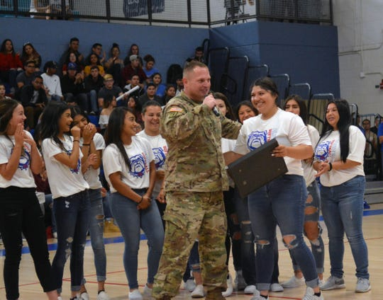 Captain Jason J. Kidd (LCHS Class of '95) presents Dezi Rae Martinez with a surprise flag that was flown over the base he was stationed at last spring during a class assembly on Friday morning.