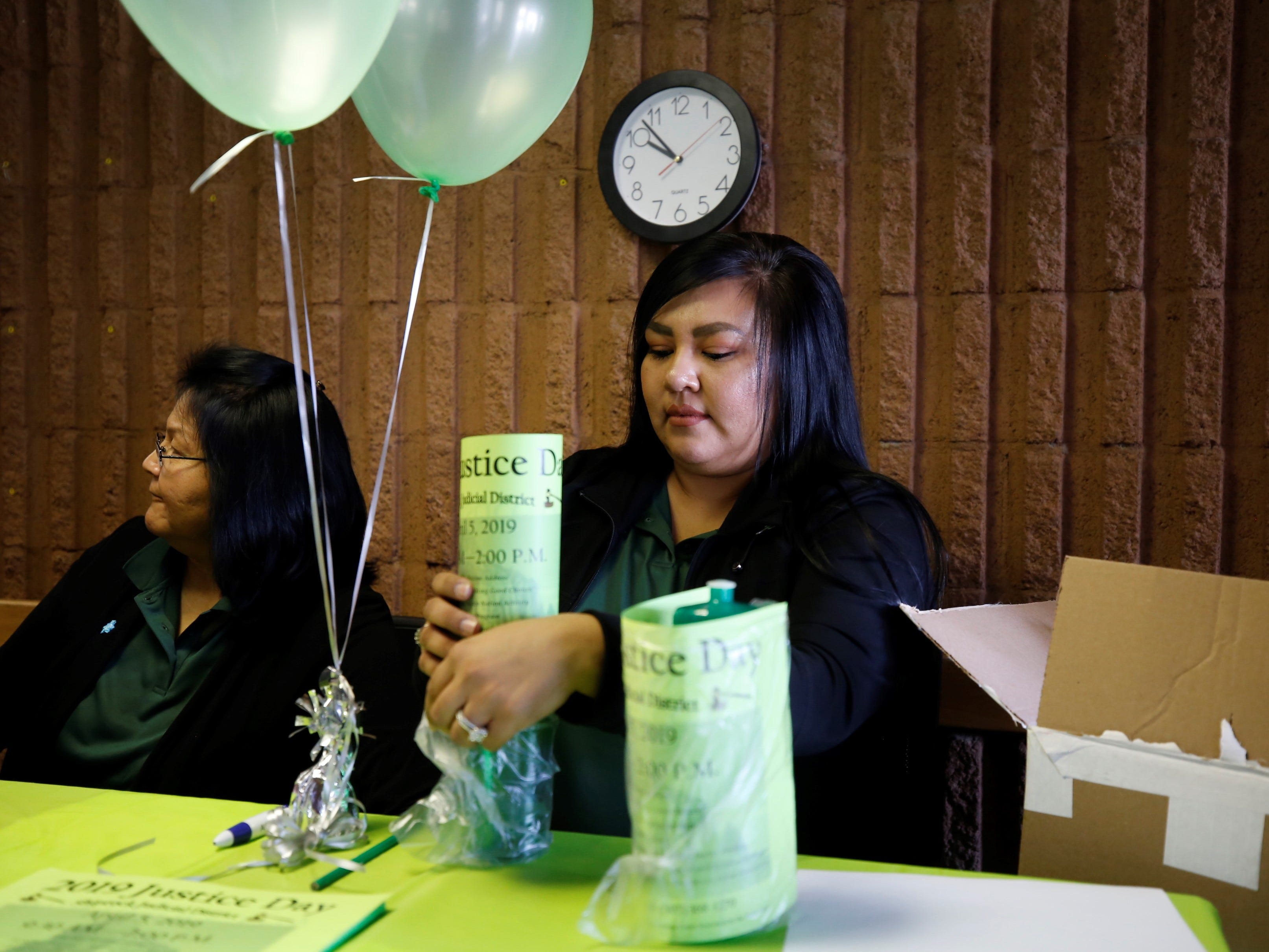 Shiprock Judicial District court employee Marla Lansing readies water bottles to give out to visitors during Justice Day at the court in Shiprock on Friday.