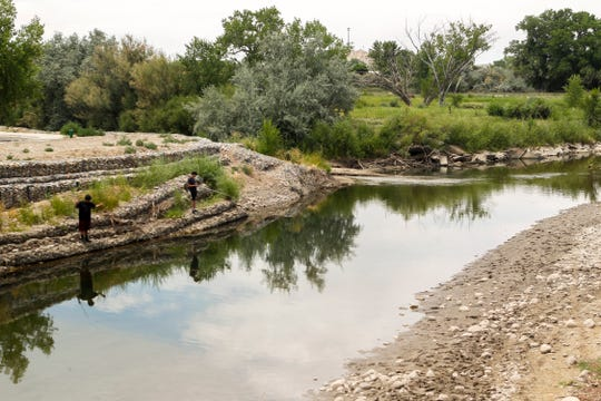 The City of Aztec may partner with San Juan Soil and Water Conservation District, Basin Hydrology and Cottonwood Consulting to remove concrete blocks and junk from the Animas River in Riverside Park and in Rio de Animas Park. In this 2018 file photo, a group fishes in the river at Riverside Park in Aztec.