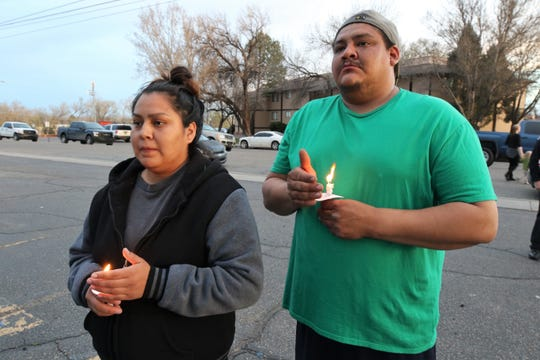 Marissa Etcitty, left, and Billy Freeman, right, hold their candles during a vigil for five-year-old Azarius Lamotte Thursday evening at the Village Apartment complex. Lamotte's father, Fernando Azofeifa, is accused of murdering his son.