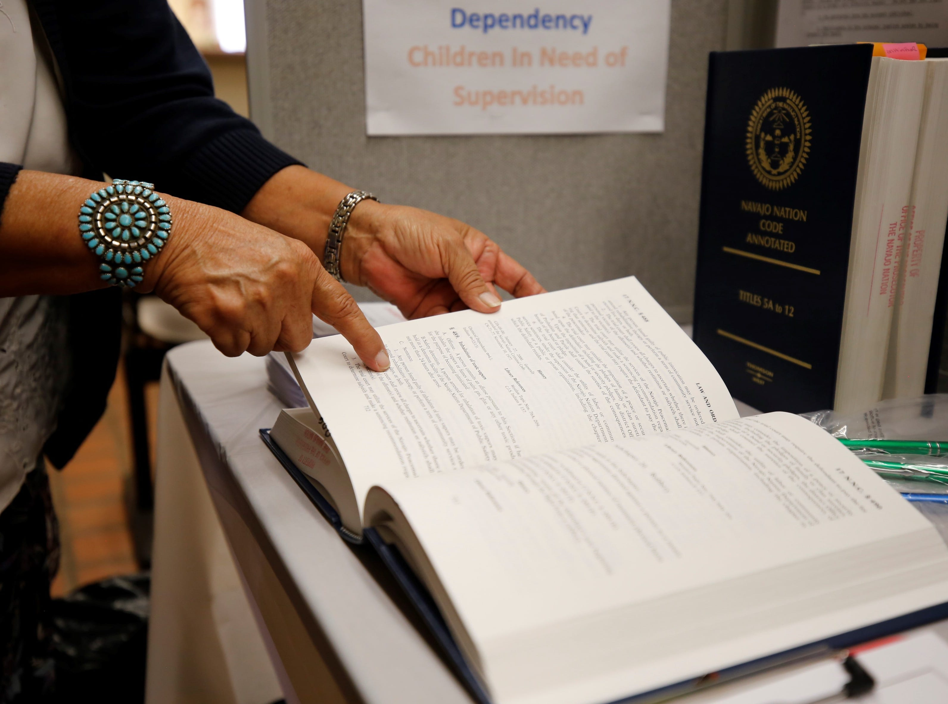 Barbara Peterson, legal secretary with the prosecutor's office for the Shiprock and Aneth district, points to the law and order section of the Navajo Nation Code during Justice Day at the Shiprock Judicial District court on Friday.
