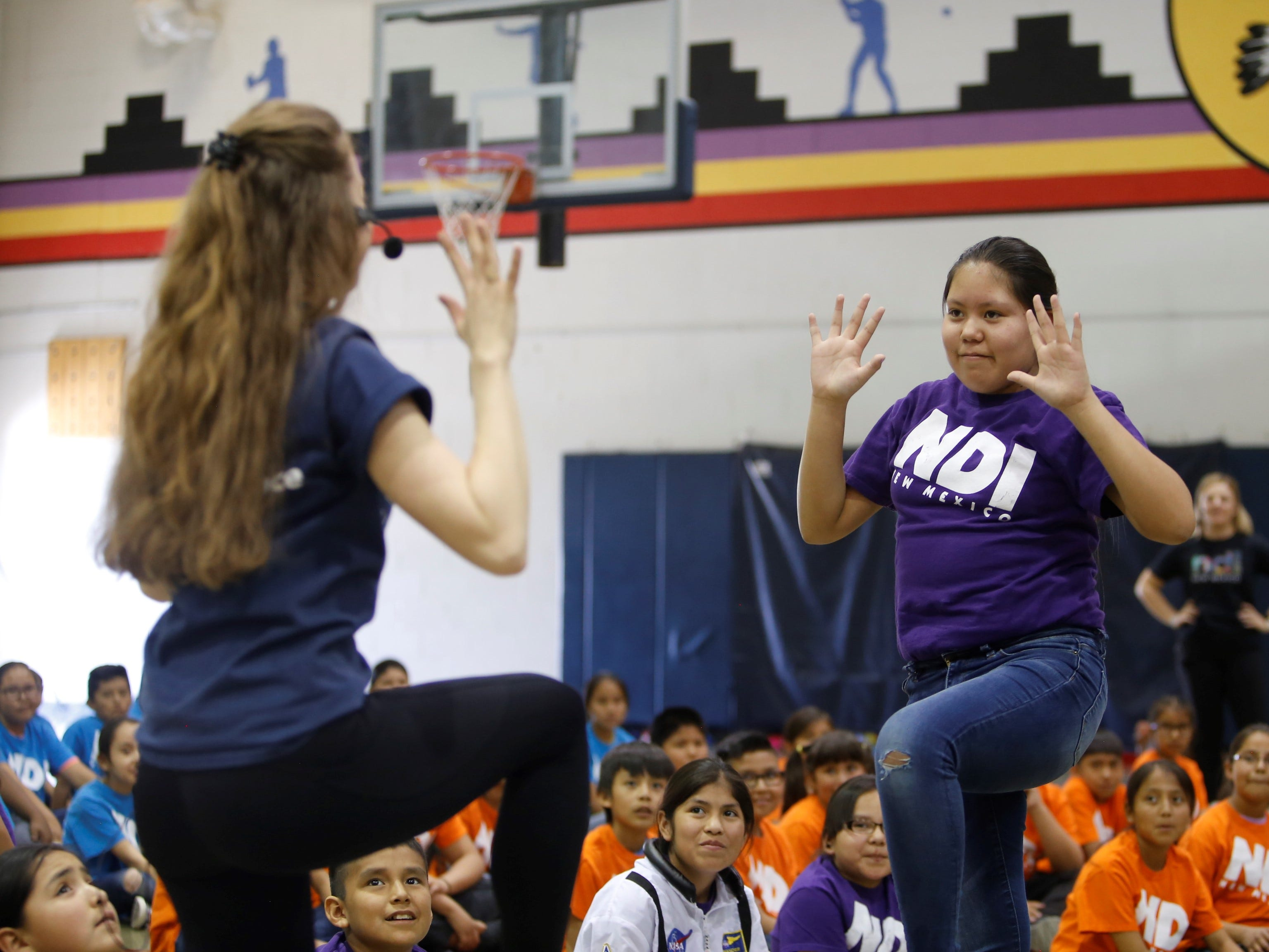 Kiera Foster, right, follows Emma Raker, residency apprentice with NDI New Mexico, during a performance on Friday at Atsá Biyáázh Community School in Shiprock.