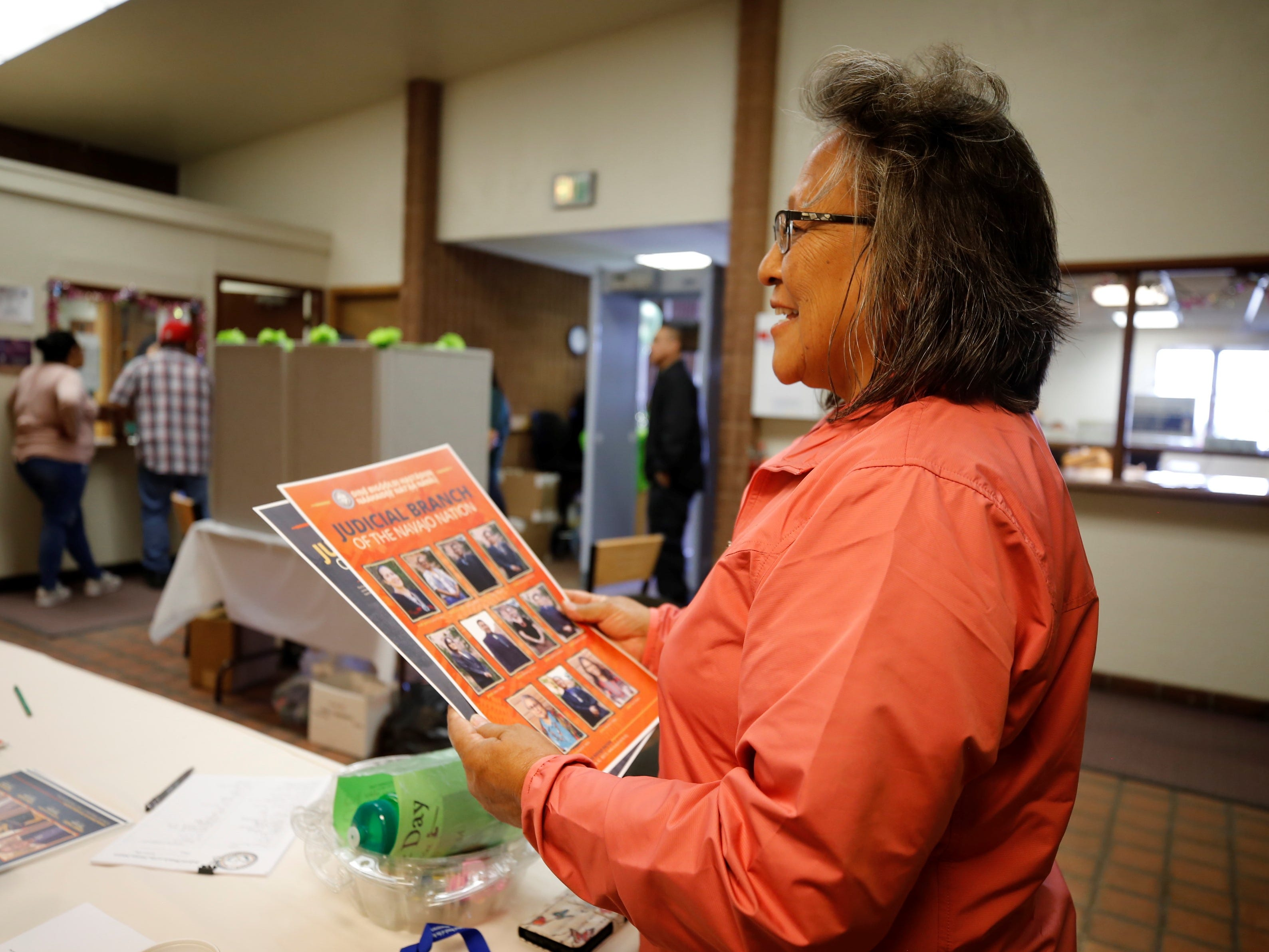 Pauline Yazzie visits former coworkers at the booth for the Administrative Offices of the Courts on Friday at Justice Day in Shiprock.