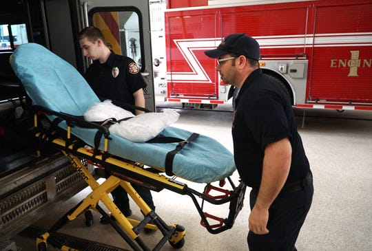 Milford EMT and firefighters Derek Gilley, left, and Chris Chappell take a stretcher out of one of their rigs at Fire Station #1 on West Huron.