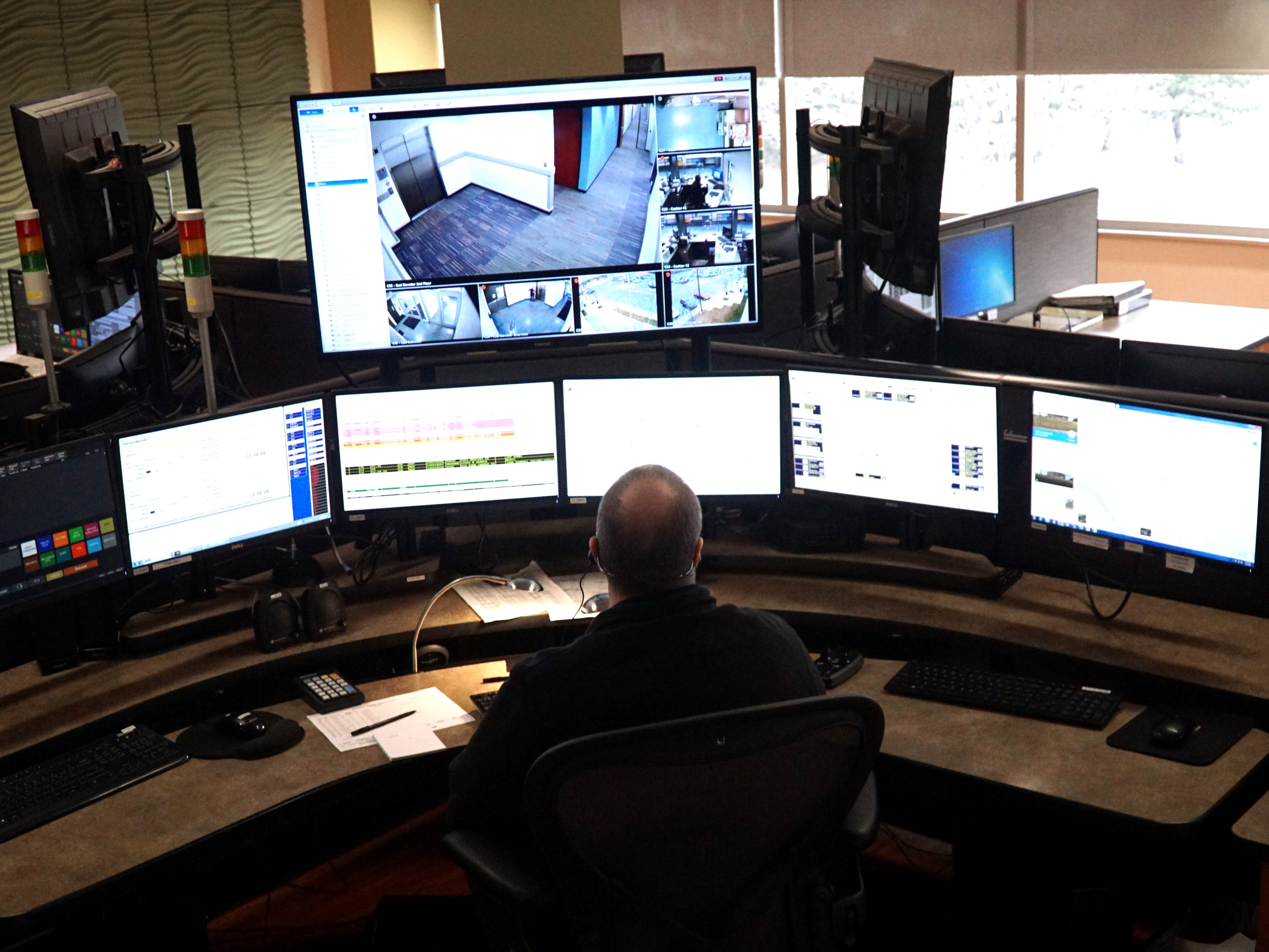 Dearborn dispatcher Brian Black stares at rows of monitors as he handles 911 calls on April 4.