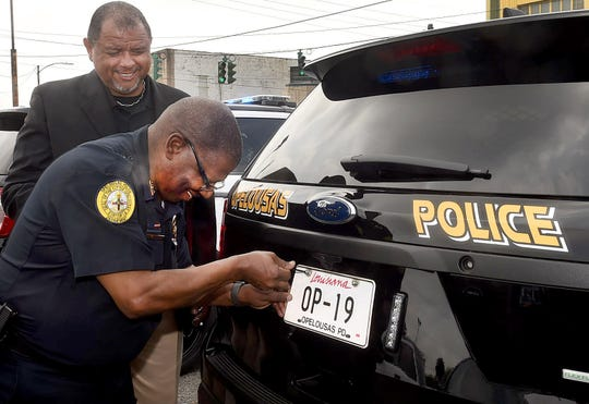 Mayor Julius Alsandor watches as Opelousas Police Chief Martin McLendon attaches a plate to one of the 14 new patrol vehicles that were released to OPD officers Friday afternoon.