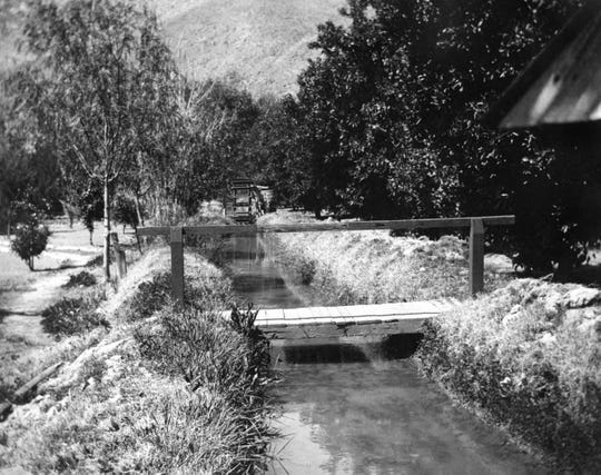 A waterwheel and a footbridge of the Tahquitz Ditch circa 1898.