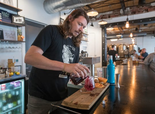 Garden & Grain beverage director Nate Simmons adds hibiscus tea as he creates a Trinidadian Punch cocktail at Perfect Plain in downtown Pensacola on Friday, April 5, 2019.