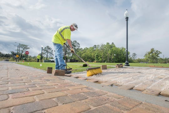 City landscaper Travis Zirker sweeps sand grout in between newly placed pavers as part of the $250,000 renovation at Jernigan's Landing in downtown Milton on Friday.