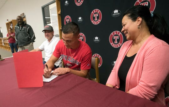 Tate High School track and field standout, Joey Zayszly, signs with the University of South Alabama as his mother and father look on during a ceremony at Tate on Friday, April 5, 2019.