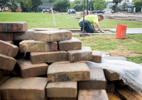 City landscaper Joshua McLendon levels the ground before installing paver inserts in the new sidewalks as part of the $250,000 renovation at Jernigan's Landing in downtown Milton on Friday.