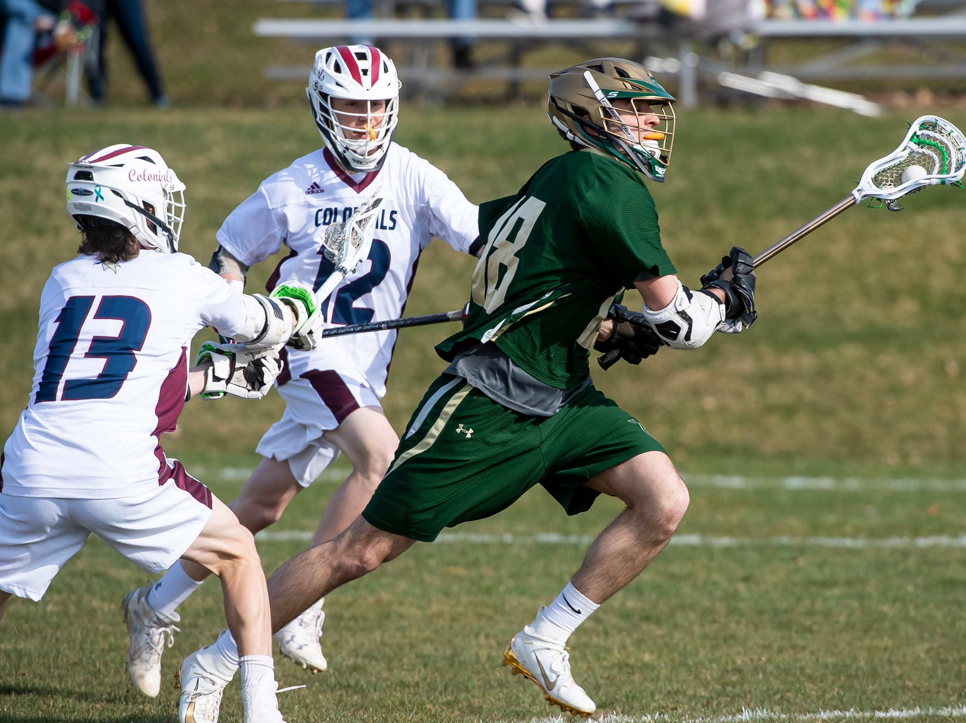 York Catholic's Cole Witman breaks through New Oxford's Connor Herring (13) and Brandon Carver (12) during a YAIAA boys' lacrosse game on Thursday, April 4, 2019. York Catholic won 14-8.