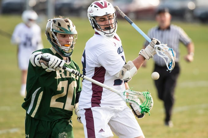 York Catholic's Brennan Witman (20) knocks the ball out of New Oxford's L. Lorderello's possession during a YAIAA boys' lacrosse game on Thursday, April 4, 2019. York Catholic won 14-8.