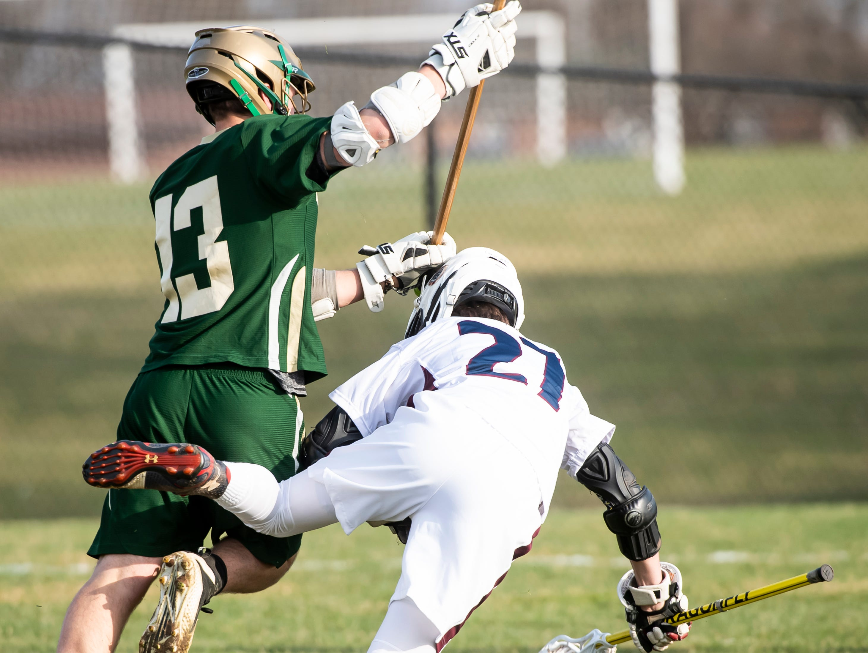 York Catholic's Ricky Pokrivka body checks New Oxford's Dylan Forbes during a YAIAA boys' lacrosse game on Thursday, April 4, 2019. York Catholic won 14-8.