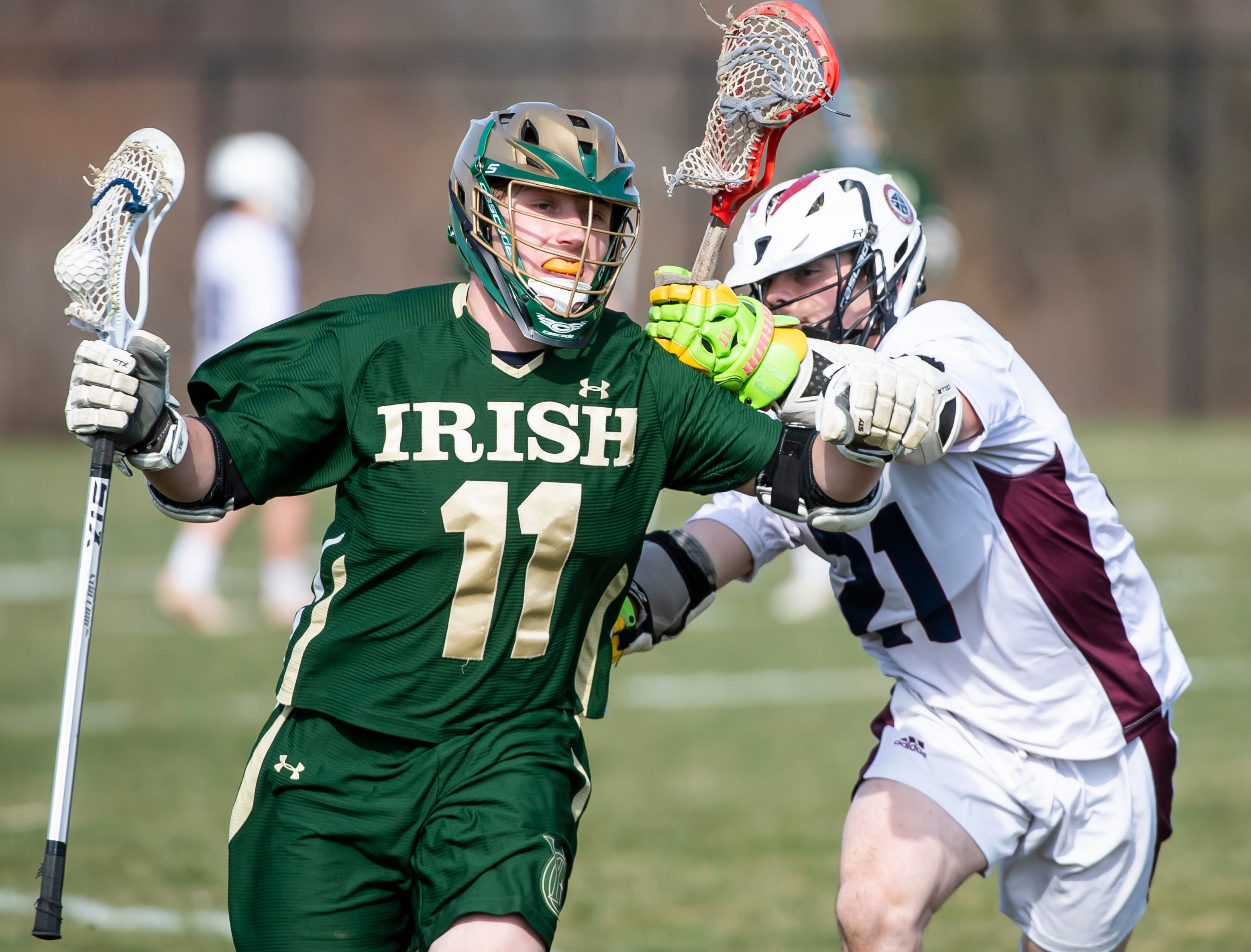 New Oxford's Dylan Forbes puts a check on York Catholic's Drew Snelbaker (11) during a YAIAA boys' lacrosse game against York Catholic on Thursday, April 4, 2019. York Catholic won 14-8.