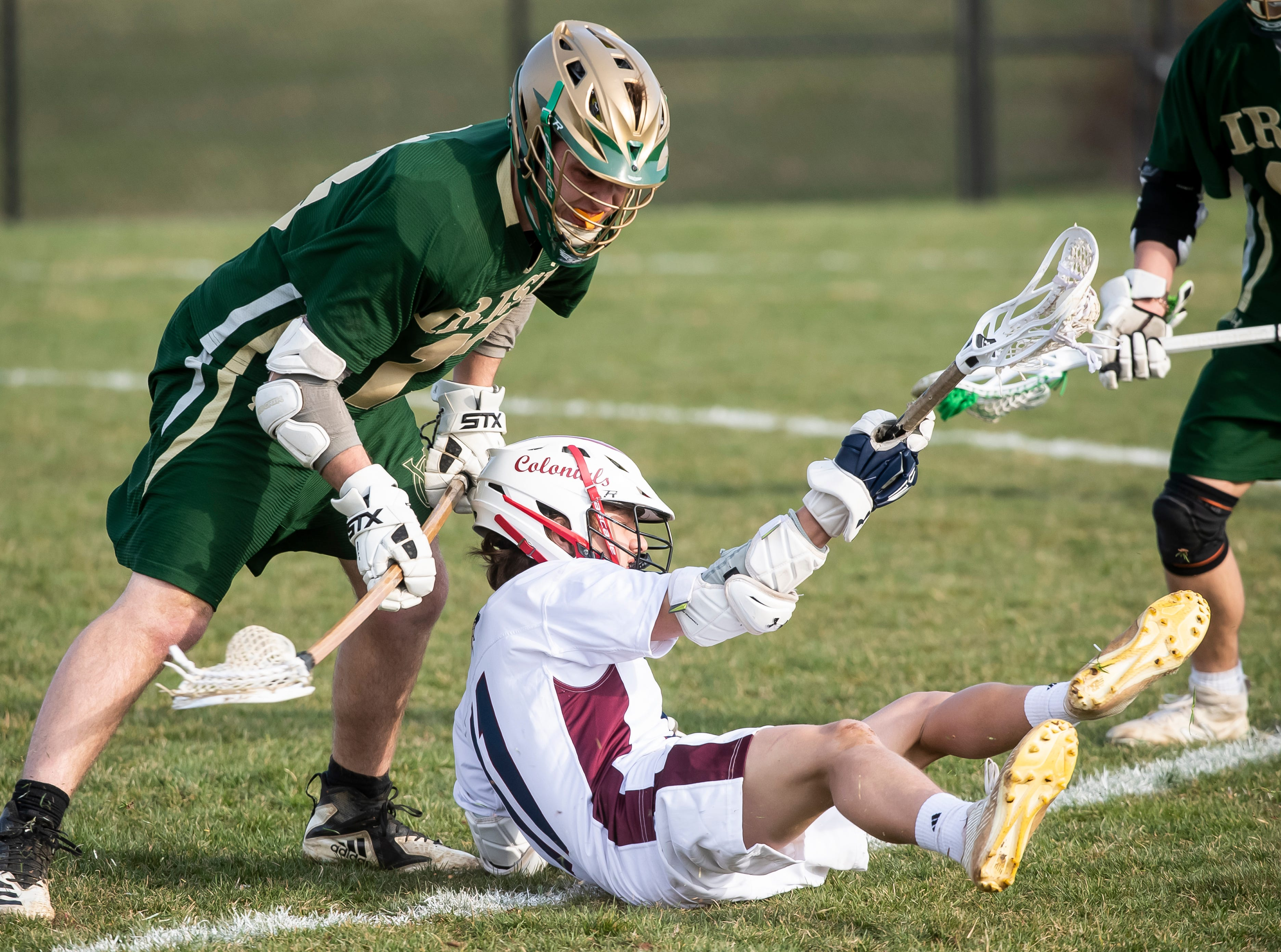 New Oxford's Lance Beckner holds onto the ball while falling to the ground during a YAIAA boys' lacrosse game against York Catholic on Thursday, April 4, 2019. York Catholic won 14-8.
