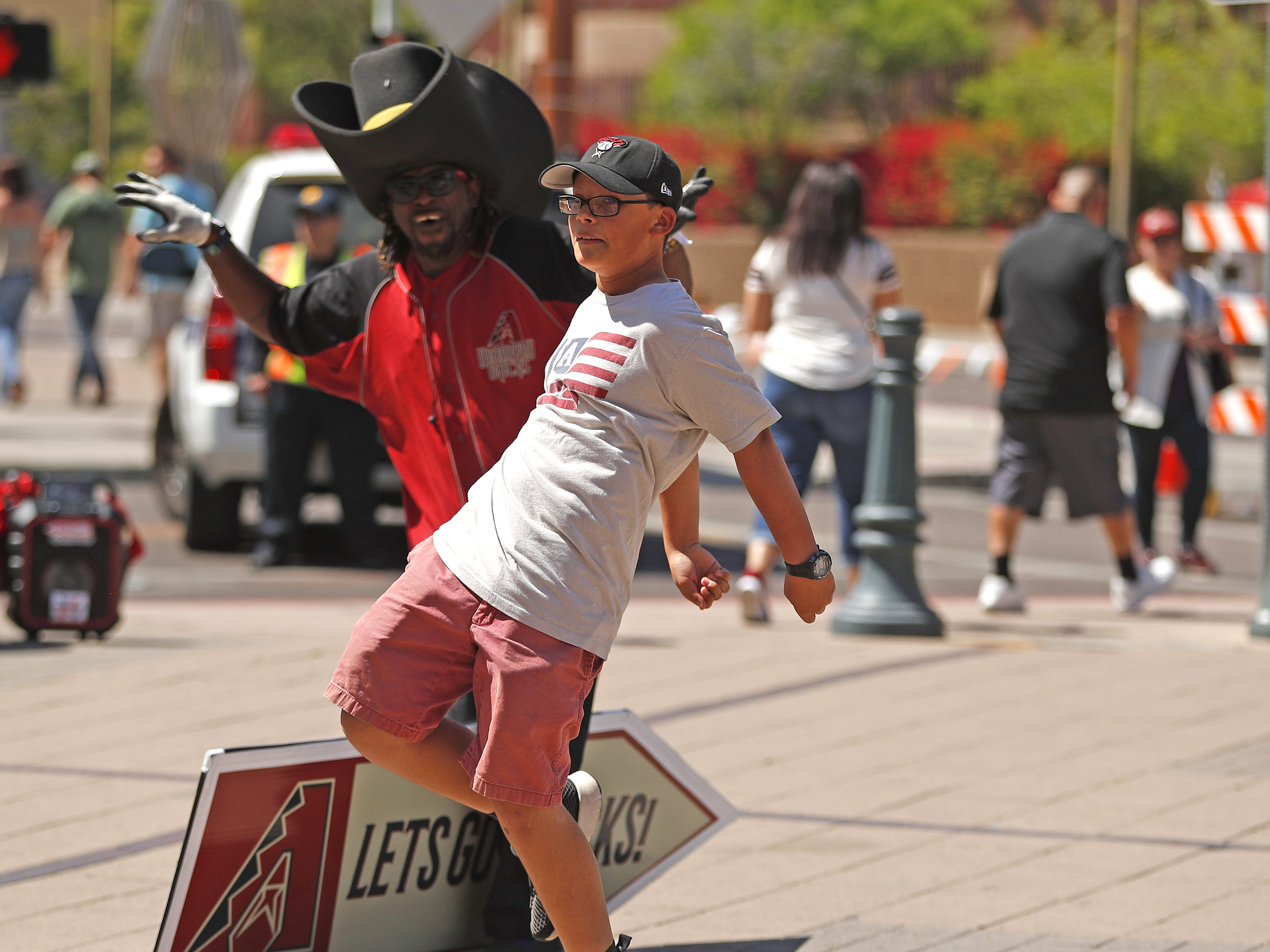 Nathan Cota, 11, dances with Diamondback Bamm outside Chase Field on the Opening Day for the Diamondbacks in Phoenix, Ariz. on April 5, 2019.