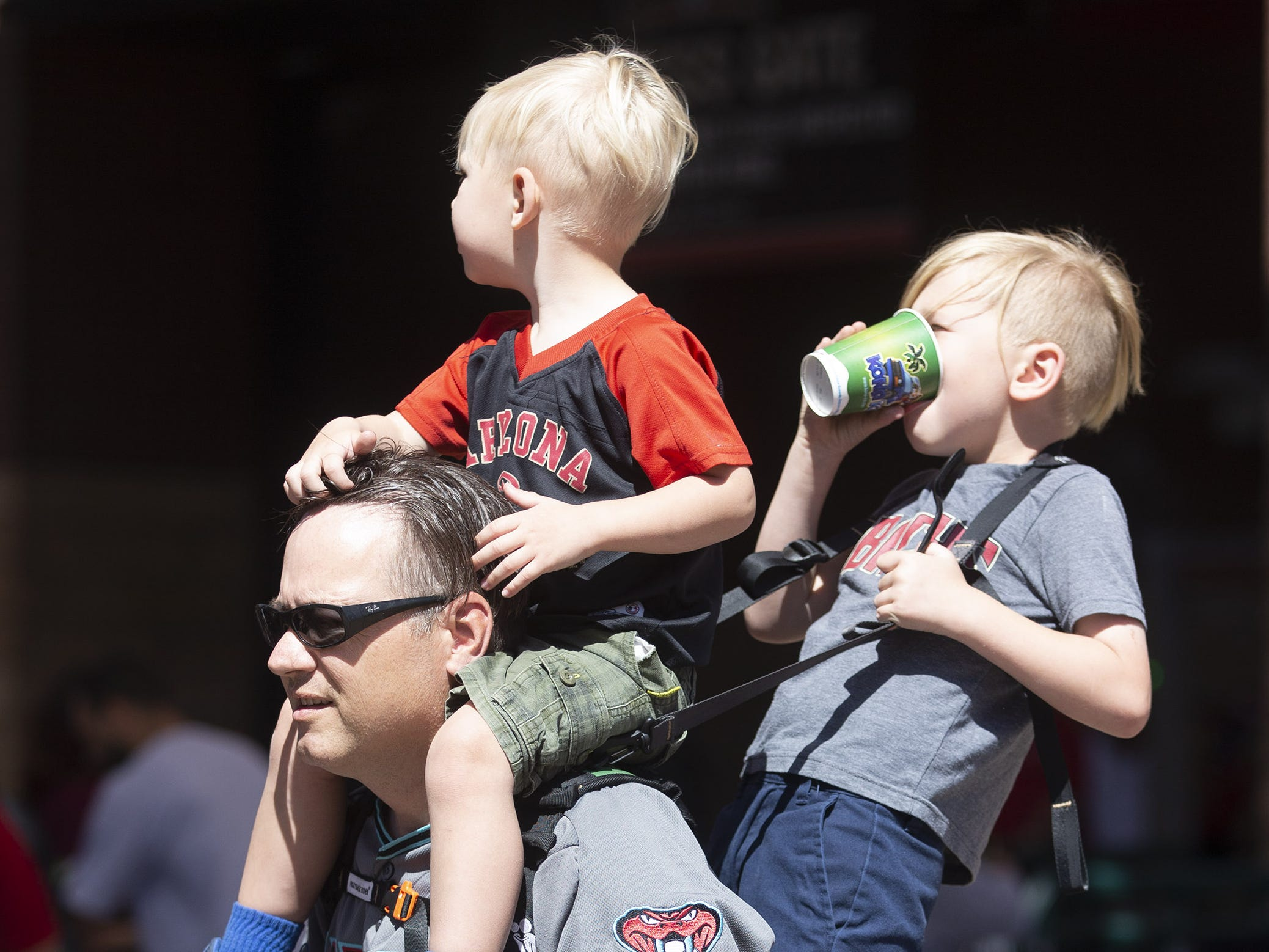 Patrick Flannagan, of Mesa, carries his sons Finn, 3, and Liam, 6, on his back during Opening Day at Chase Field in Phoenix on April 5.
